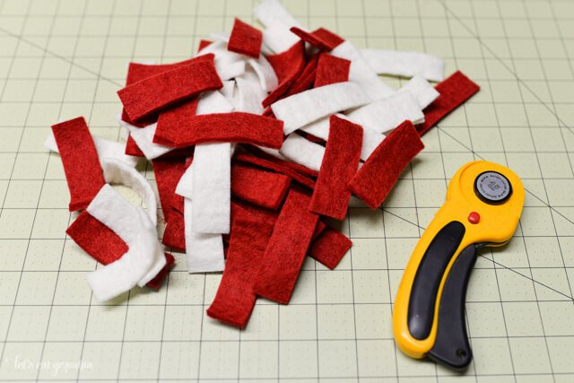 rotary cutter, cutting mat and strips of white and red felt cut