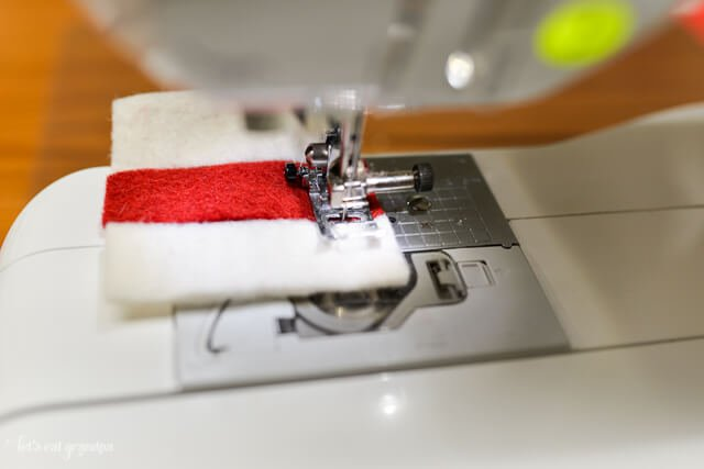 sewing machine sewing red and white felt strips together