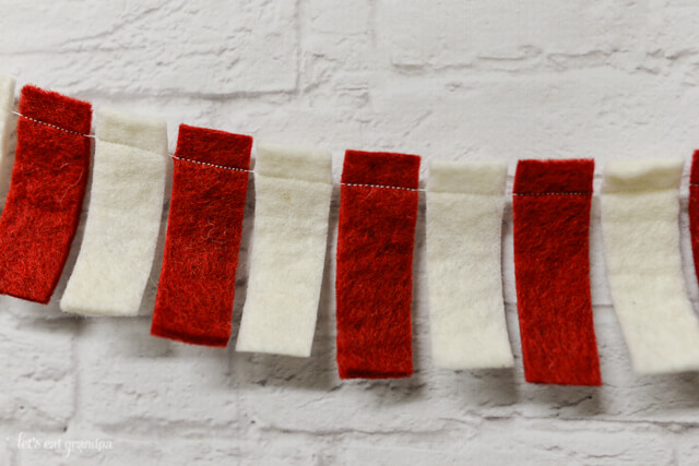 Fifteen minutes and two colors of felt and you can easily make this fun and festive candy cane garland. Would be great for a Dr. Seuss Cat in the Hat party as well! #Christmas #Garland #CraftLightning