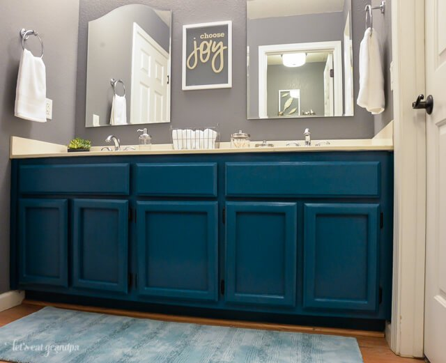 Choose joy floating artwork in bathroom above teal cabinets