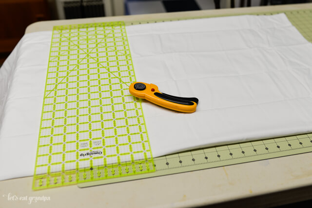 measuring old shower curtain and flat sheet with rotary cutter