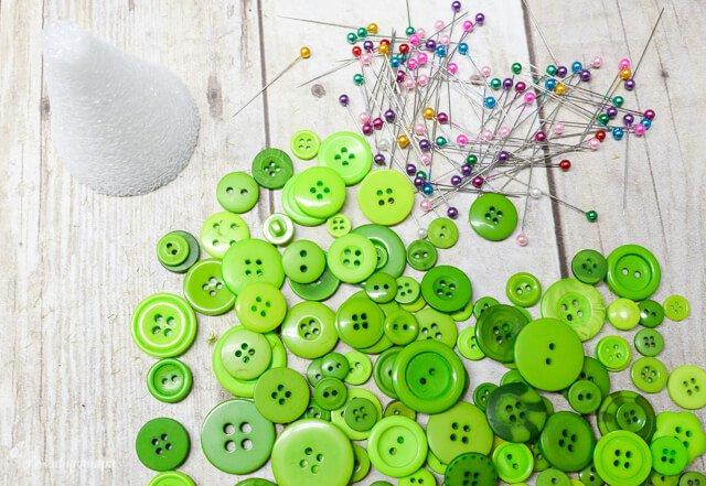 Supplies needed for Button Christmas tree craft: buttons, pins, and foam cone