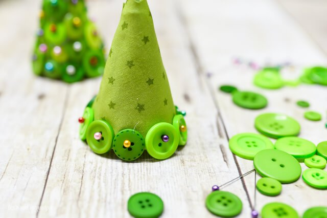 row of buttons placed on fabric cone to make Christmas button foam craft