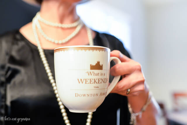 woman holding Downton Abbey tea cup and wearing pearls