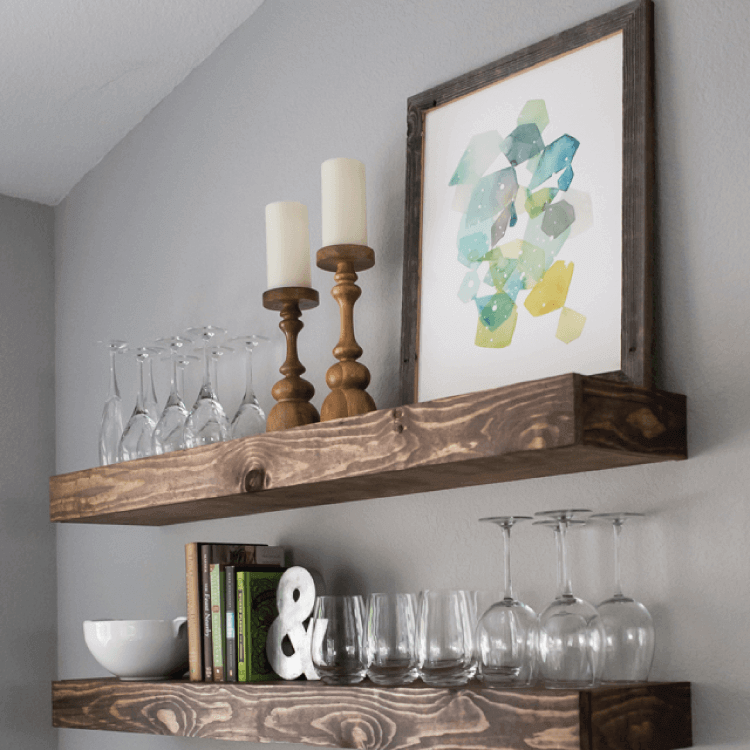 wooden floating shelves in kitchen with glasses and home decor