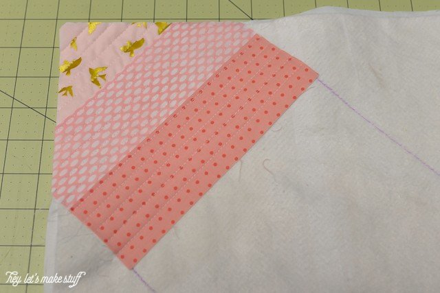 fabric layered on batting on sewing mat