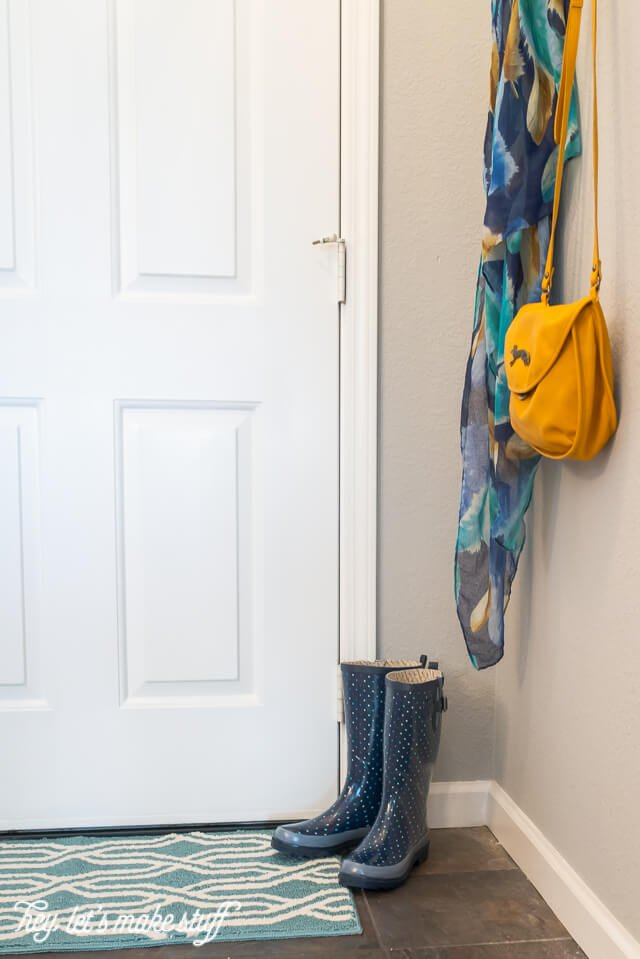 purse and scarf hanging from hooks in entryway