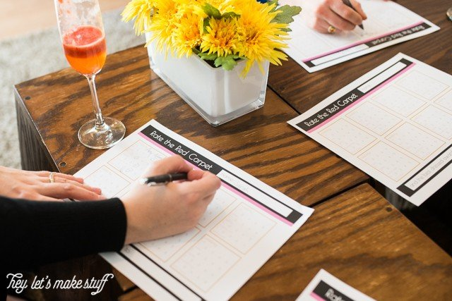 woman filling out Oscars party game printable on table