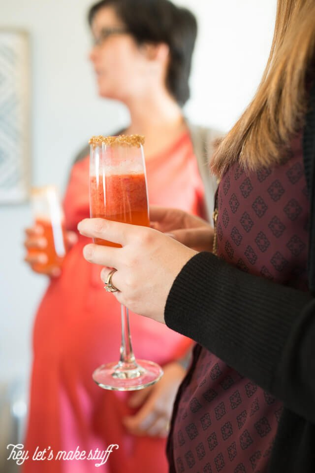 woman holding red strawberry champagne flutes