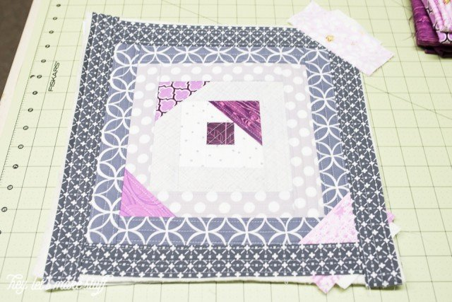 fabric squares pieced together using quilt-as-you-go method on sewing mat