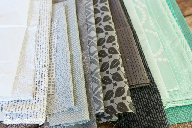 piles of various teal and gray fabric