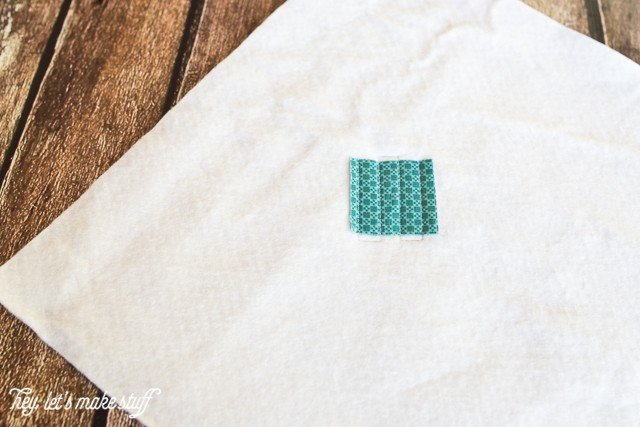 small teal fabric square on backing fabric