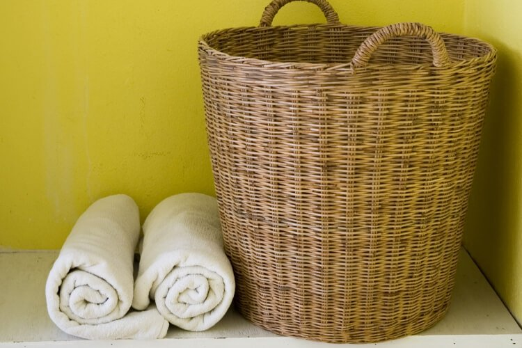 laundry basket with rolled up towels next to it