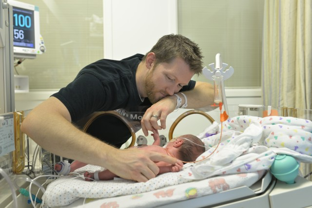 dad leaning over baby in the NICU
