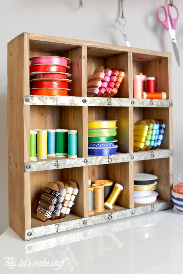 wooden cubby organizer displaying colorful ribbons and spools of thread