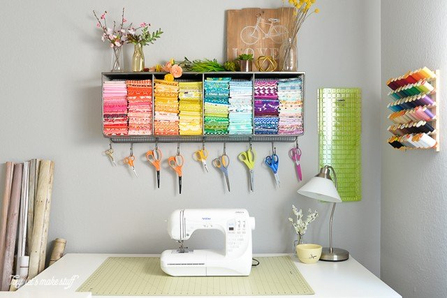 craft room with sewing machine on table and pretty colored fabrics and scissors organized above