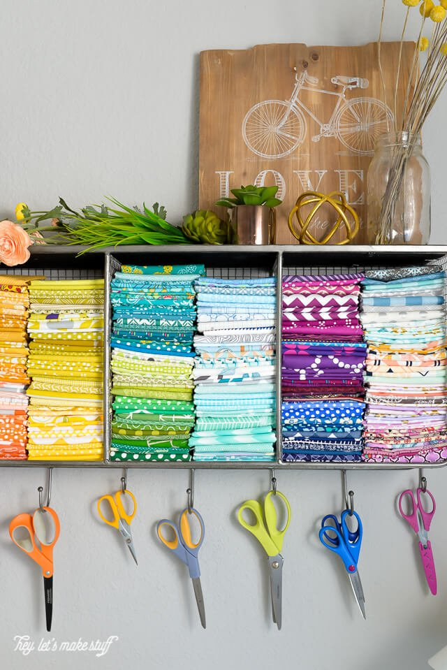 pretty colored fabric stacked in organizational wall hanging cubby