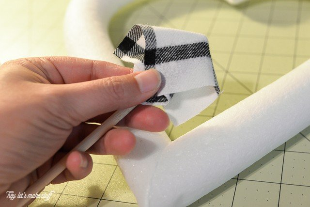foam heart and black and white fabric square folded over in woman's finger