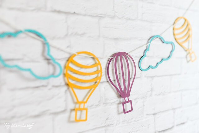side view of colorful hot air balloon and cloud SVG files cut on paper and strung against background