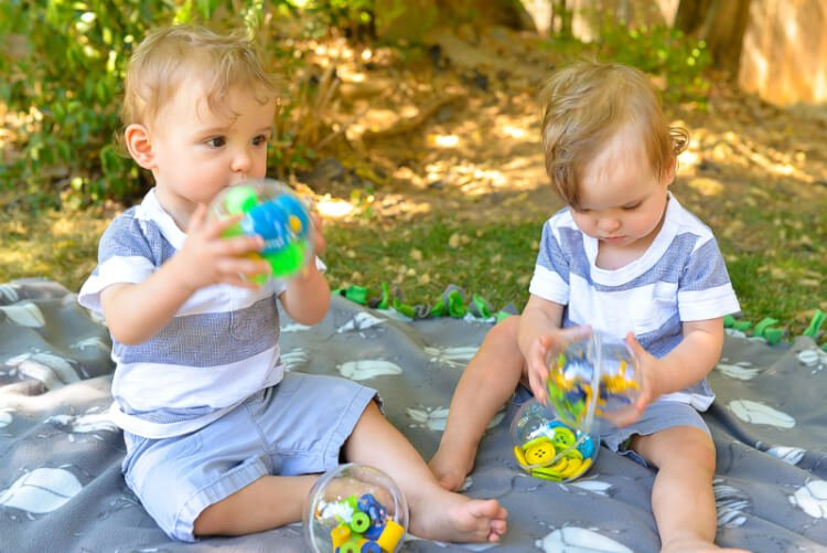 toddlers holding sound shaker toy using plastic ornaments and Gorilla Glue
