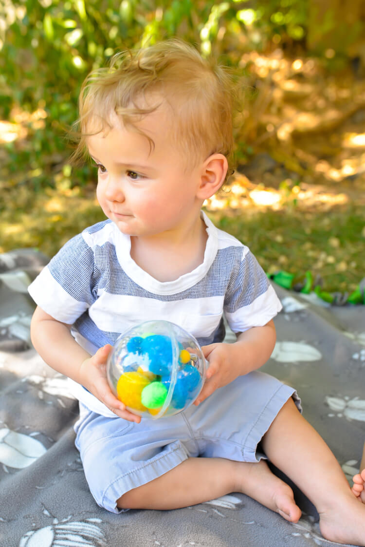 toddler holding sound shaker toy using plastic ornaments and Gorilla Glue