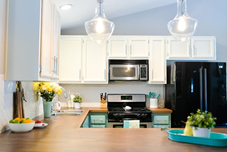 transformed dated 1980's kitchen with bright painted cabinets, new lighting, and gorgeous butcher block countertops.