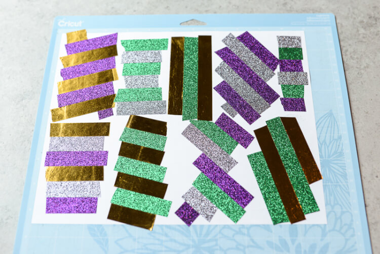 This festive Mardi Gras garland is made out of colorful washi tape! Celebrate Fat Tuesday in style with this simple craft that you can make using your Cricut Explore -- or just cut by hand!