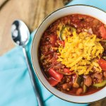 his simple but delicious vegetarian chili tastes like it simmered all day in your slow cooker, but it's made quickly in the Instant Pot! Hearty quinoa and beans and plenty of vegetables means this dish can stand on its own for dinner. Leave off the cheese and it's vegan!