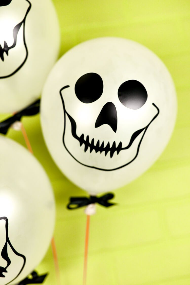 These Easy Skull Balloons from heyletsmakestuff.com are a fun Halloween party decoration! Whip up a bunch using your Cricut and these free SVG cut files.