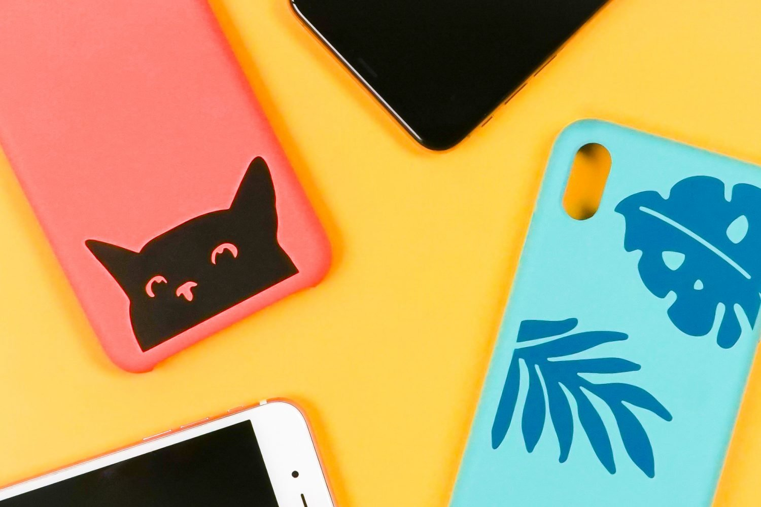 Phone cases made with a Cricut on a yellow background