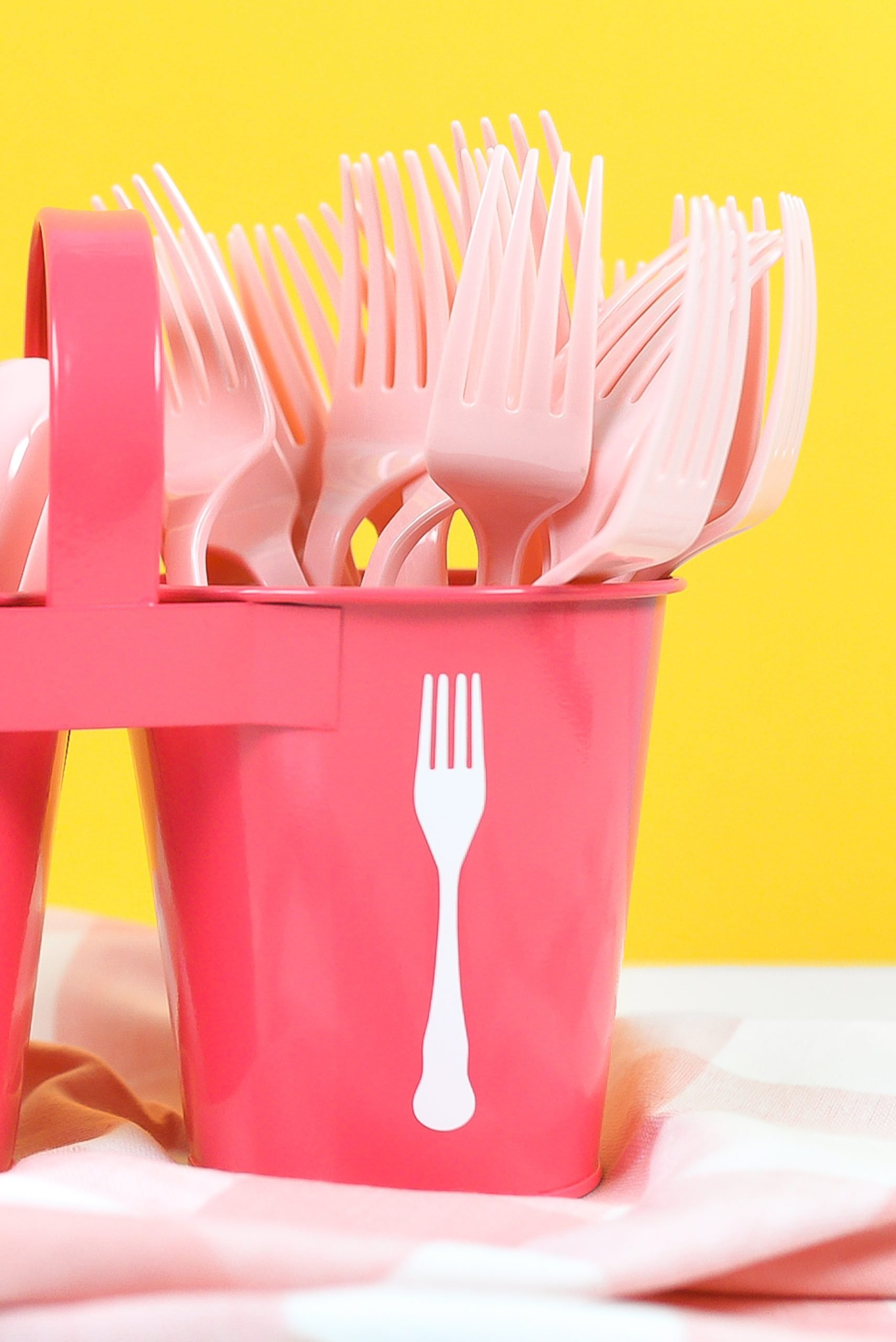 Zoomed in shot of pink utensil caddy with white spoon and for decals, filled with pink plastic forks and spoons on a yellow background.