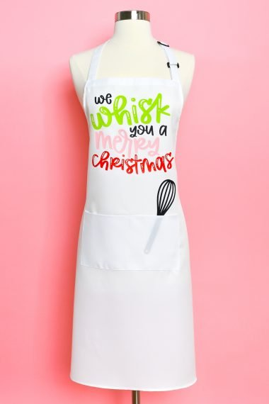 """If your favorite place to be during the holidays is in the kitchen, you need a Christmas apron! Make this cute """"We whisk you a merry Christmas"""" apron using your Cricut Explore or Cricut Maker!"""