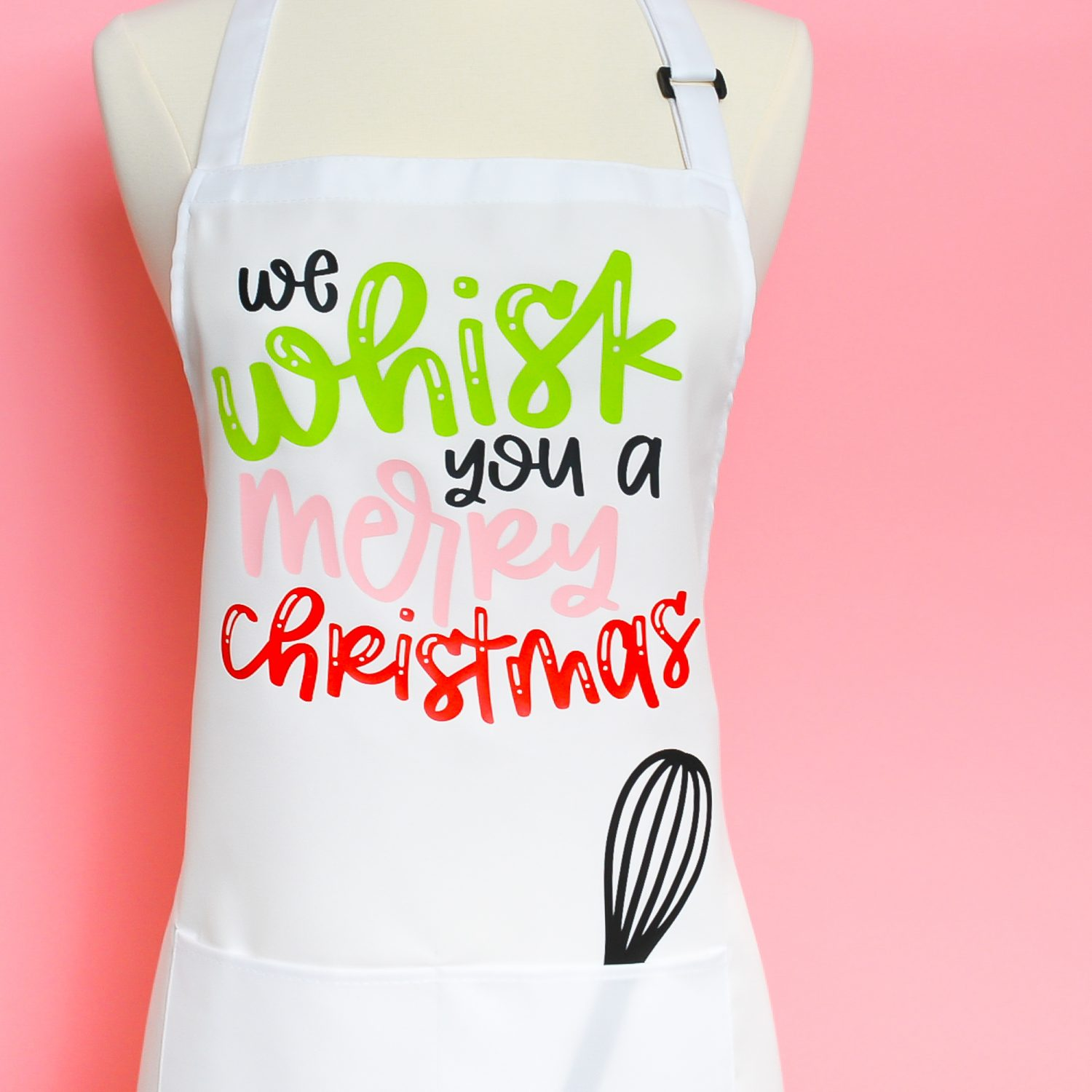 """White apron with """"We Whisk You a Merry Christmas"""" on pink background."""