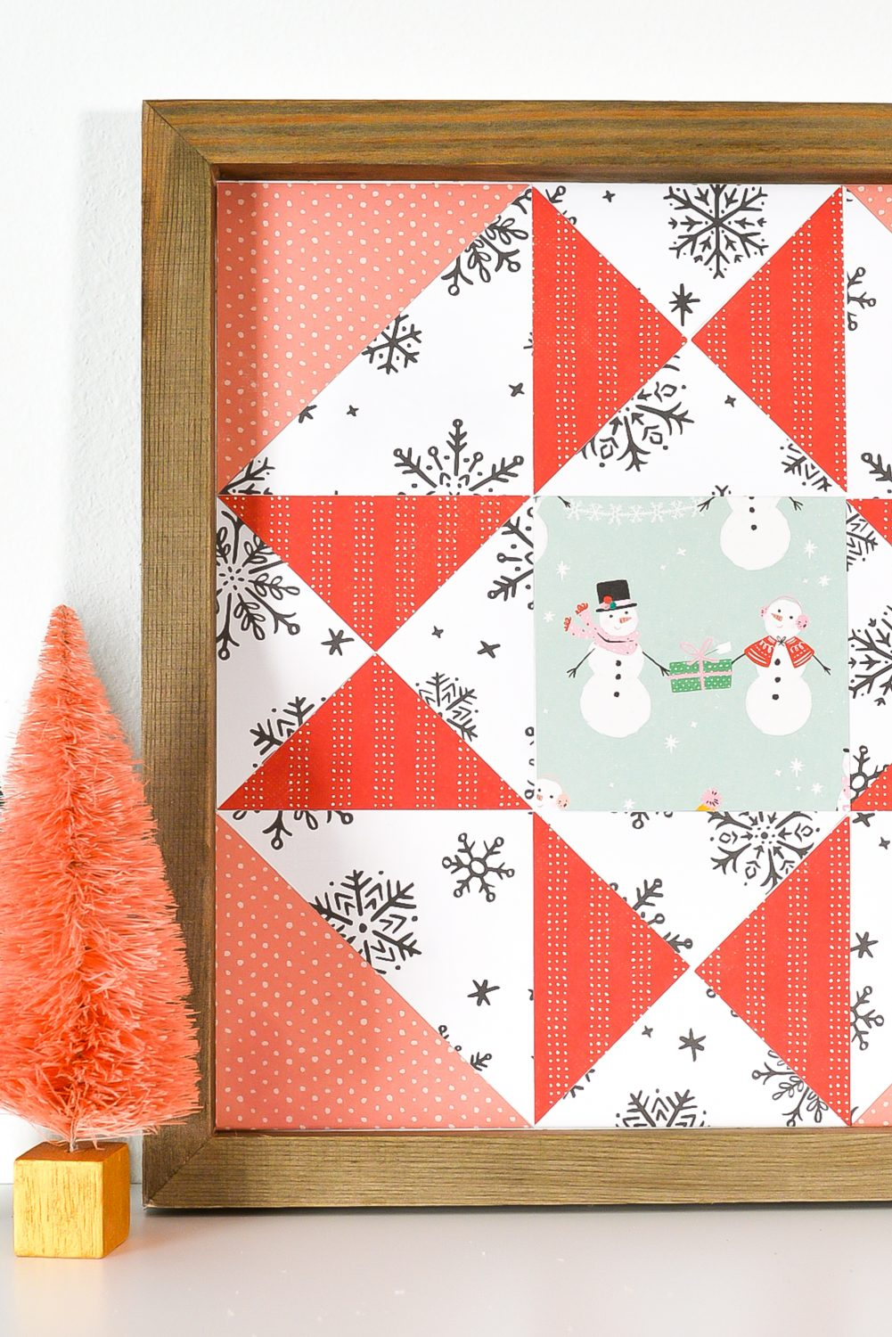 Closeup of Christmas Paper Quilt Block on shelf with faux tree decor