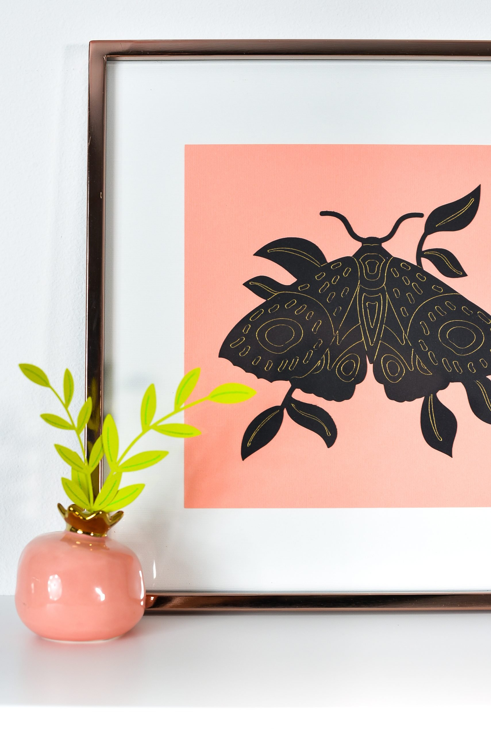 Moth artwork on shelf with small paper plant