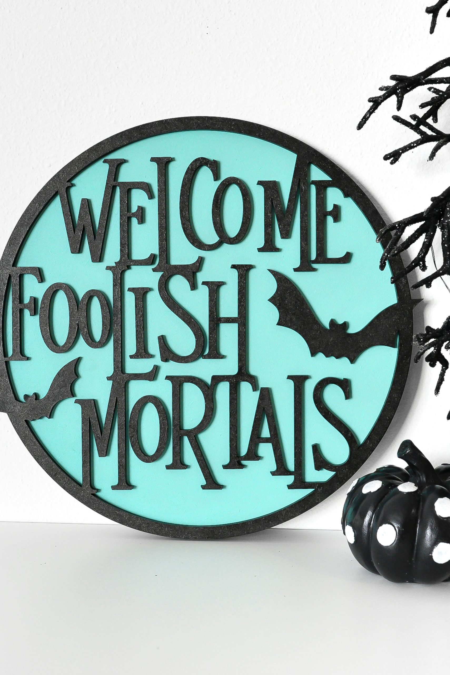 """Welcome Foolish Mortals"" sign made on the Glowforge on a shelf with Halloween decor"