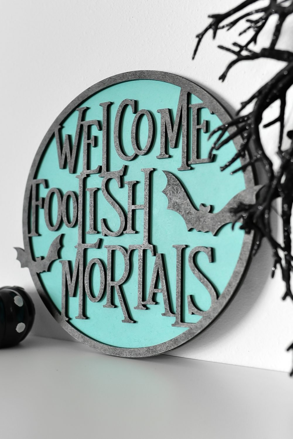Angled shot of Welcome Foolish Mortals sign on a shelf with Halloween decor