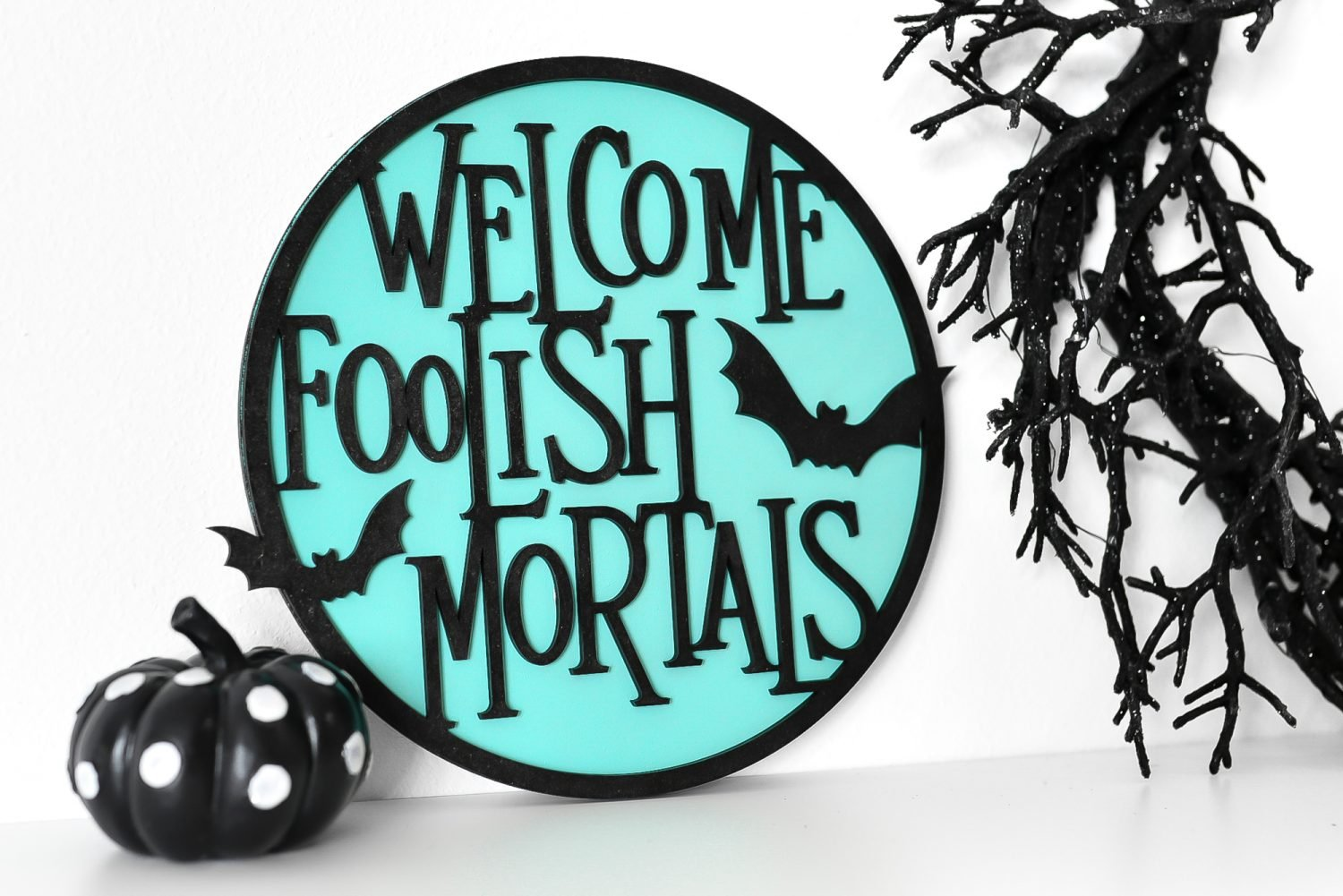 Welcome Foolish Mortals sign on a shelf with Halloween decor