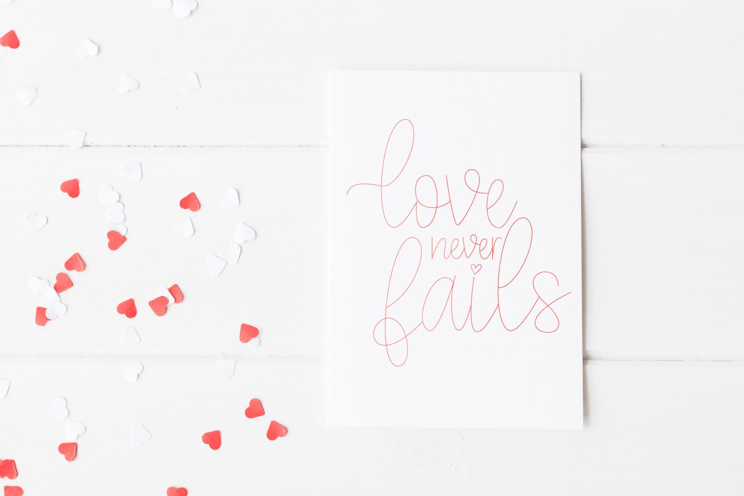 Love Never Fails foiled on a card.