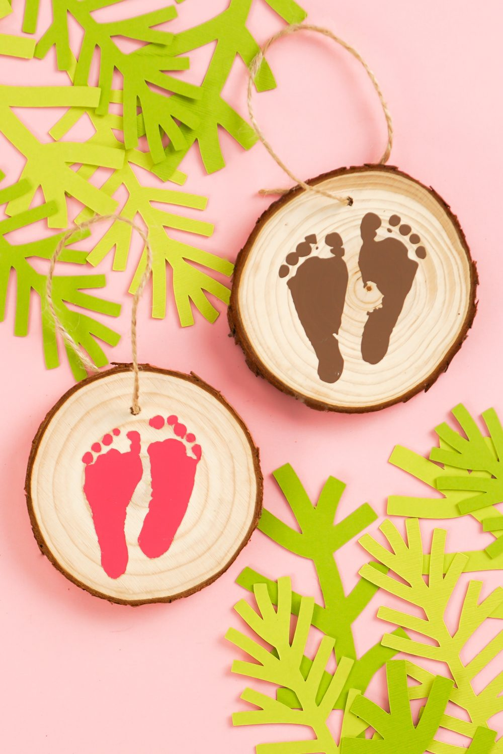 Closeup of footprint ornaments on pink background.