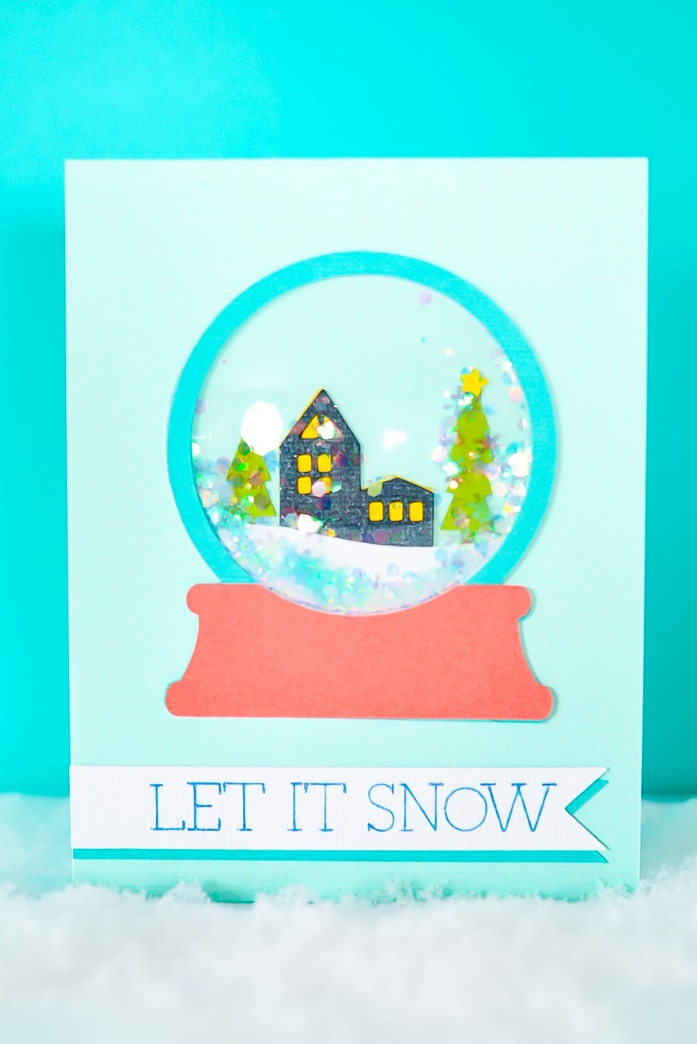 Finished snowglobe shaker card with fame snow and blue background.