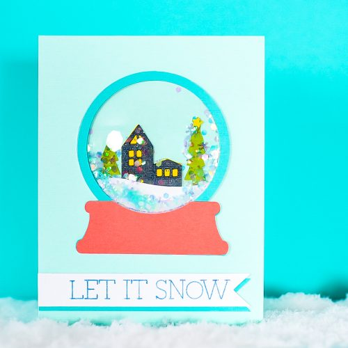 Finished snow globe shaker card on a blue background.