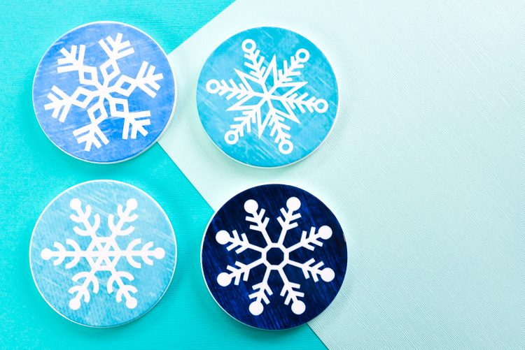Need a place to set down that mug of hot cocoa or mulled wine? Make these bright and cheery snowflake Christmas coasters using Cricut Infusible Ink!