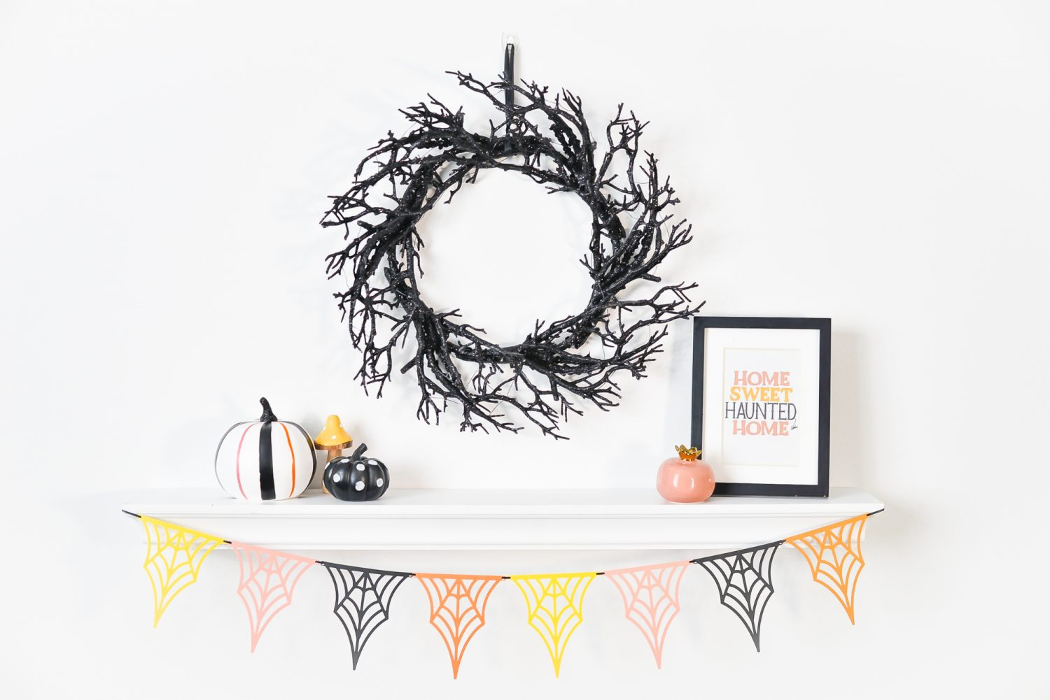 Spider web banner hanging from shelf with Halloween decorations