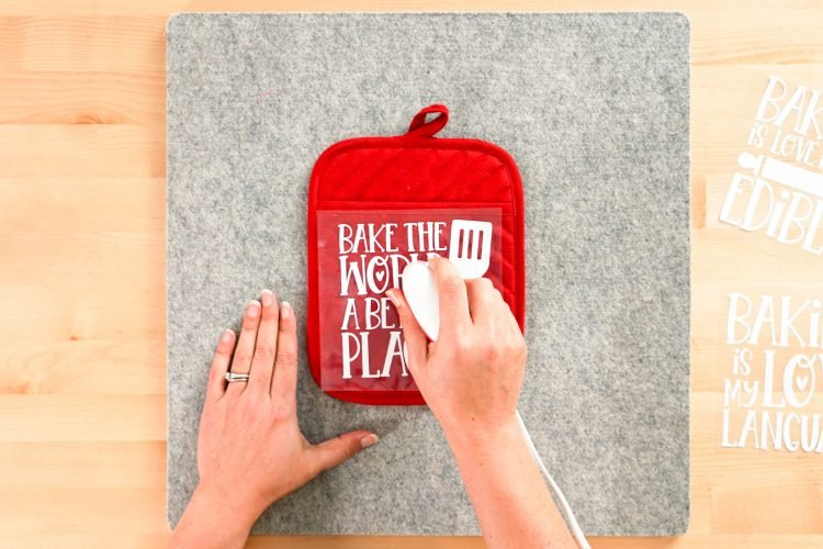Hands using EasyPress Mini to adhere decal to the potholder
