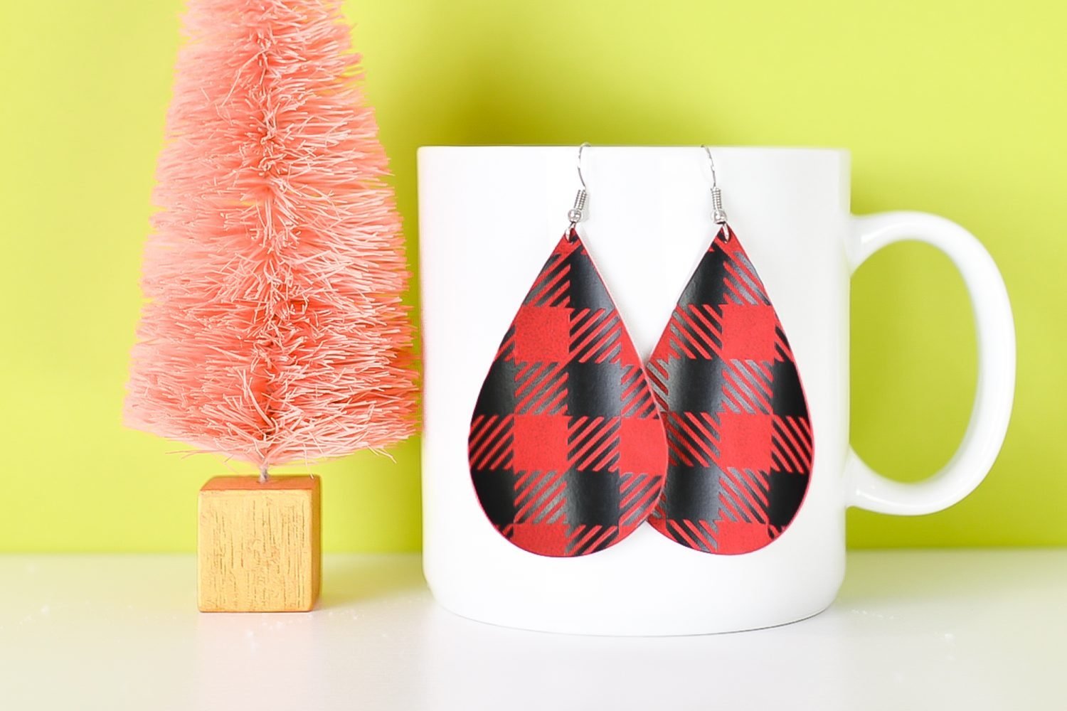 Finished red buffalo plaid earrings hanging from a coffee cup
