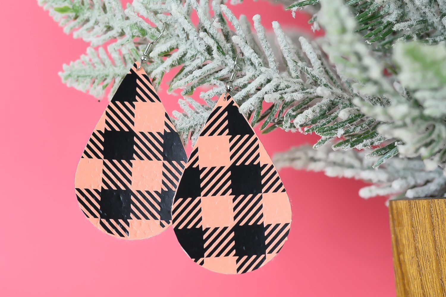 Finished pinkbuffalo plaid earrings hanging from a christmas tree branch