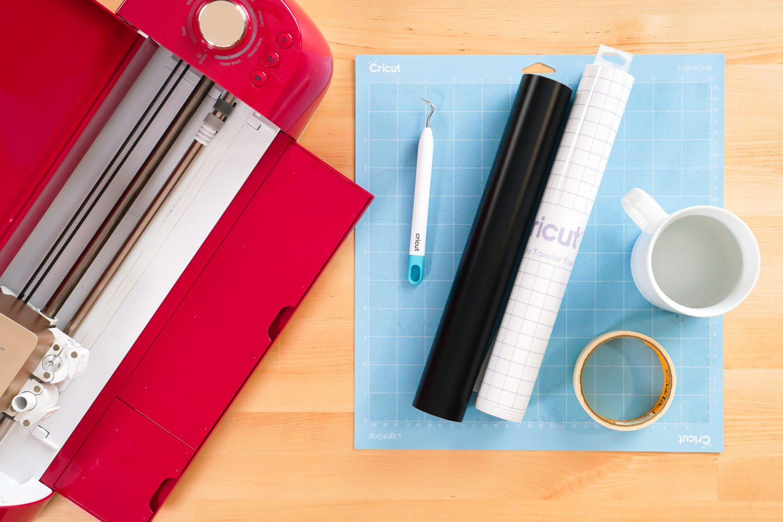 Supplies for this project: Cricut, Cricut mat, weeding tool, black vinyl, transfer tape, mug, masking tape.
