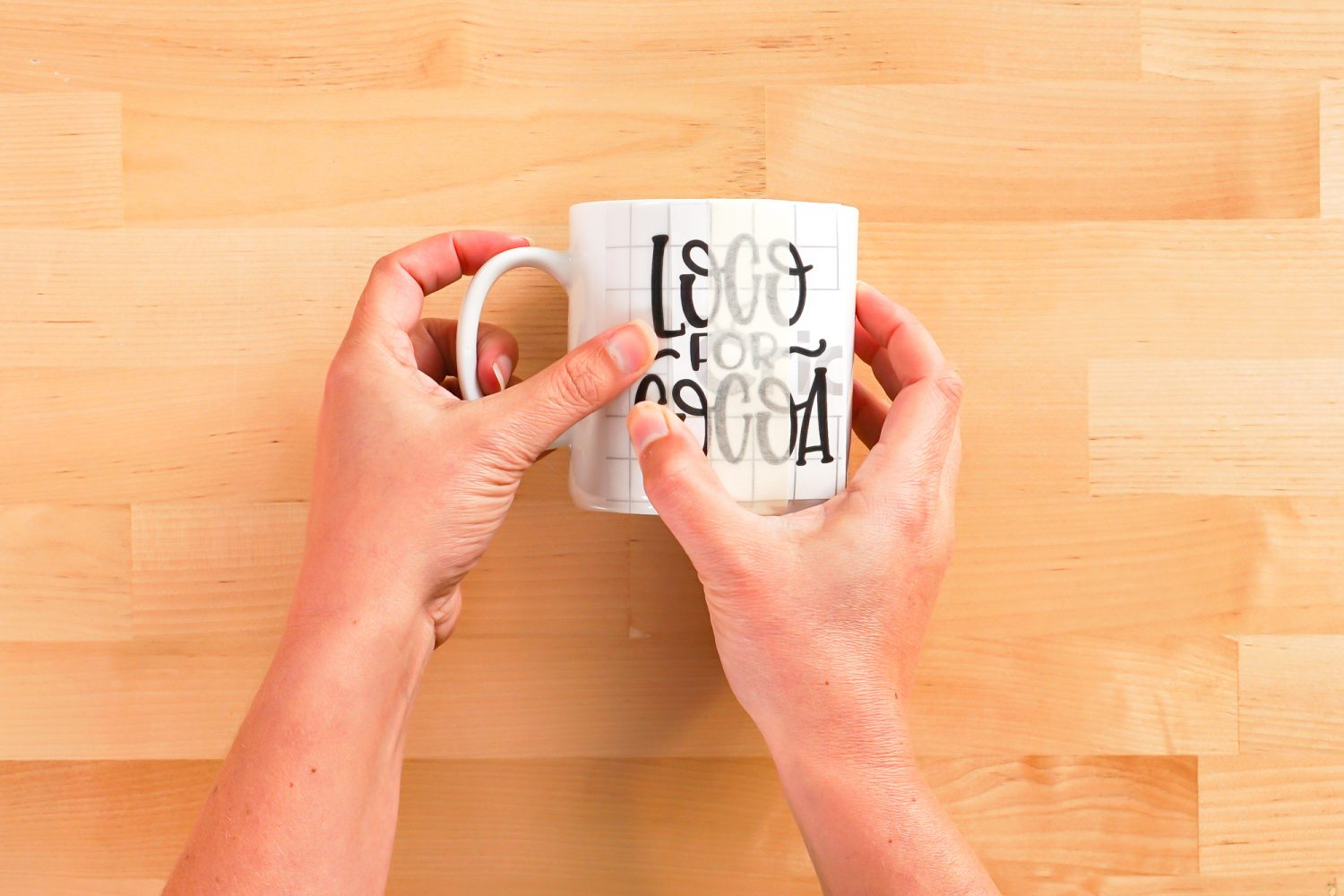 Hands placing the left side of the decal on the mug.