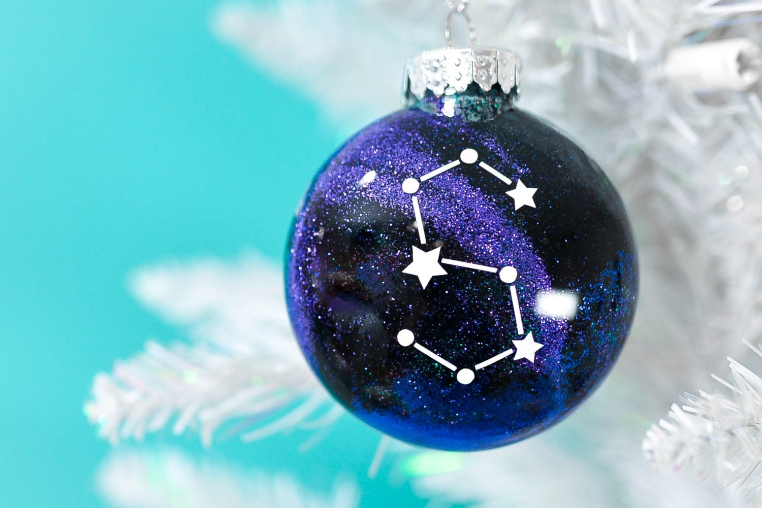 Finished constellation glitter ornament hanging from white Christmas tree